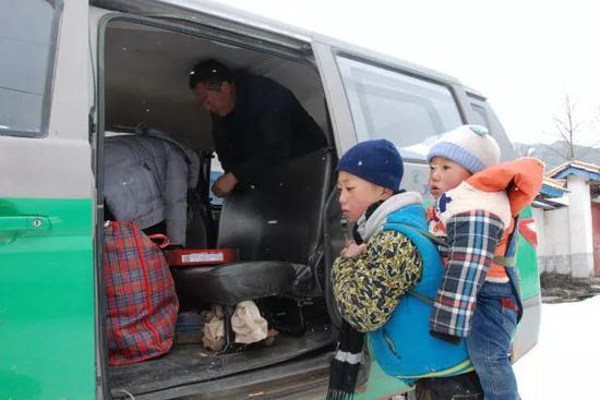 吉觉吉竹背着弟弟,登上去往申果乡沙苦新村外公家的班车。