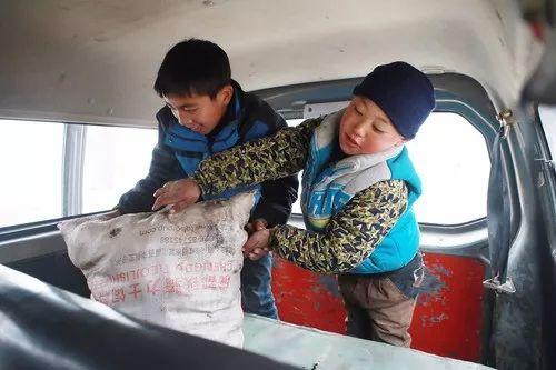 到新家后,小伙伴帮吉觉吉竹从班车往下卸土豆。