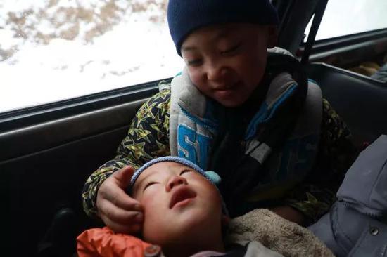 在去往申果乡沙苦新村外公家的路上,吉觉吉竹在车上逗弟弟玩。