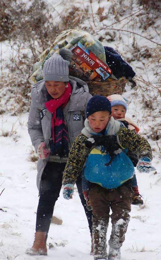 吉觉吉竹背着弟弟,和妈妈在山路上跋涉,前往申果乡沙苦新村的外公家。