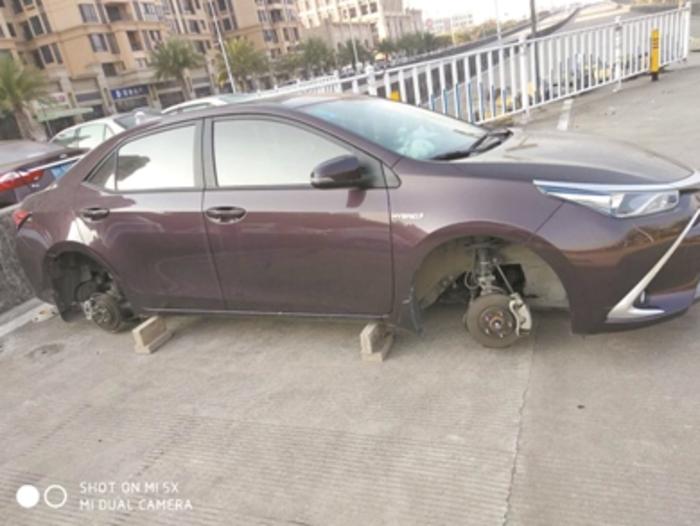 嫌疑人将车轮盗走后,用几块砖头支撑车身。