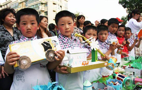 幼儿园的小朋友们展示用废品制作的小玩具