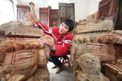 """3月18日,歙县北岸镇大阜村农民沈雁在雕刻木雕""""牛腿""""."""